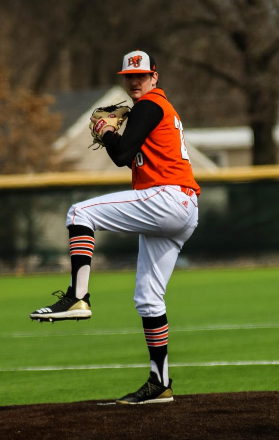 Freshman, Hunter Gudde, begins his delivery as the starting pitcher in the Wildcats conference opener.