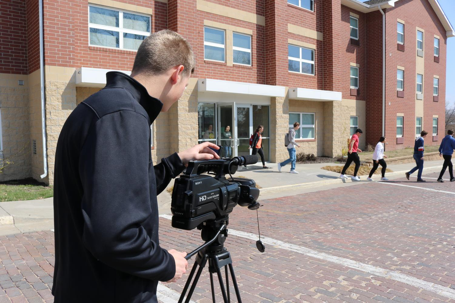 Freshman Adam Cook aims the camera at video participants. An average of 15 students were involved with each campus safety short film production.