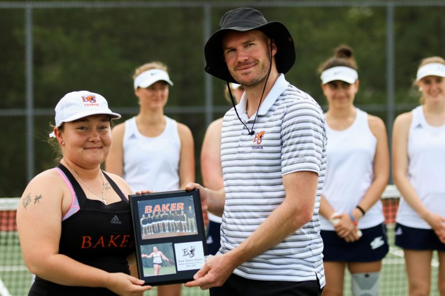 Senior, Kate Taylor-Doran receives a plaque from head coach, Keith Pipkin, honoring her achievements as a senior.