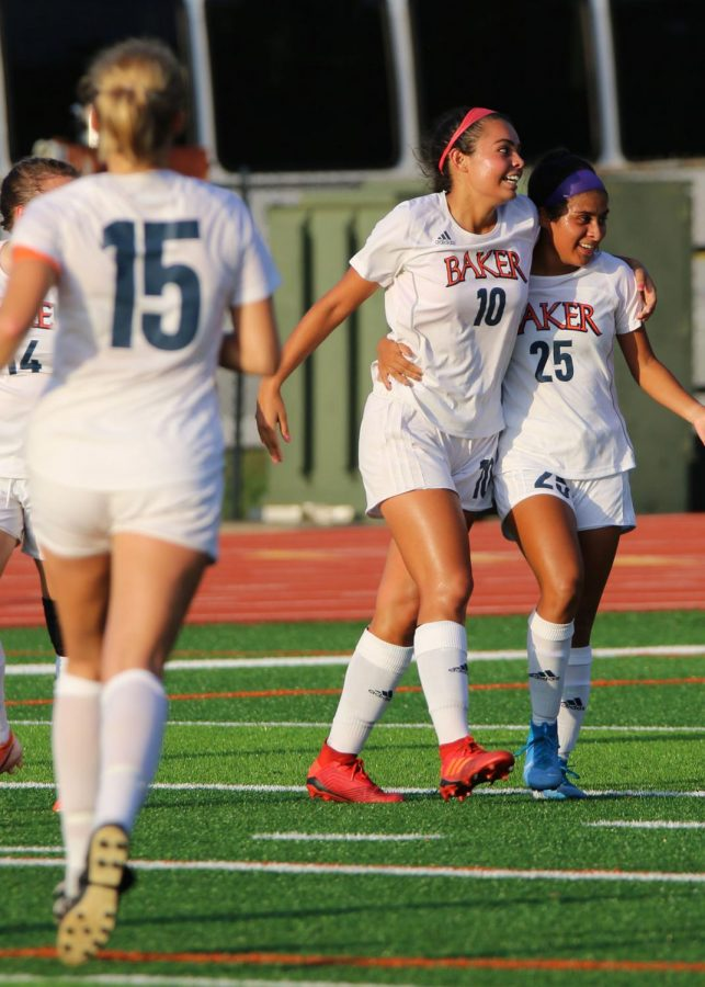 Junior and Captain Kara Knapp (left) runs to celebrate with Junior Victoria Aceves Powers (middle) and Junior Monique Diaz (right). Aceves Powers opens the scoring for Baker in the first half against William Penn University.