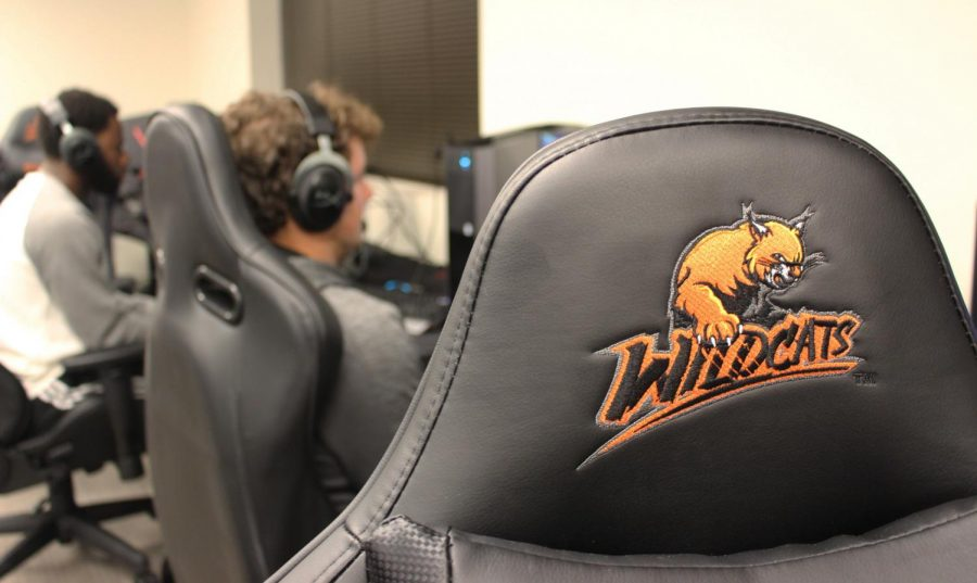 One of the Esports team's gaming chairs. While Justin Toumberlin and Will Cox compete in a Rocket League Tournament in the background.
