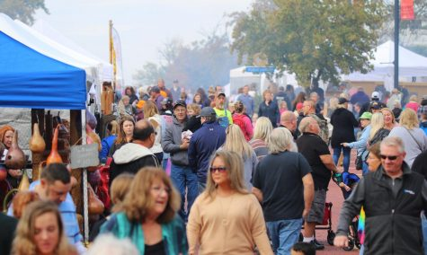 Thousands of people walking high street viewing handmade crafts and local businesses. The town of Baldwin City, KS grows in attendance each third full weekend of October.