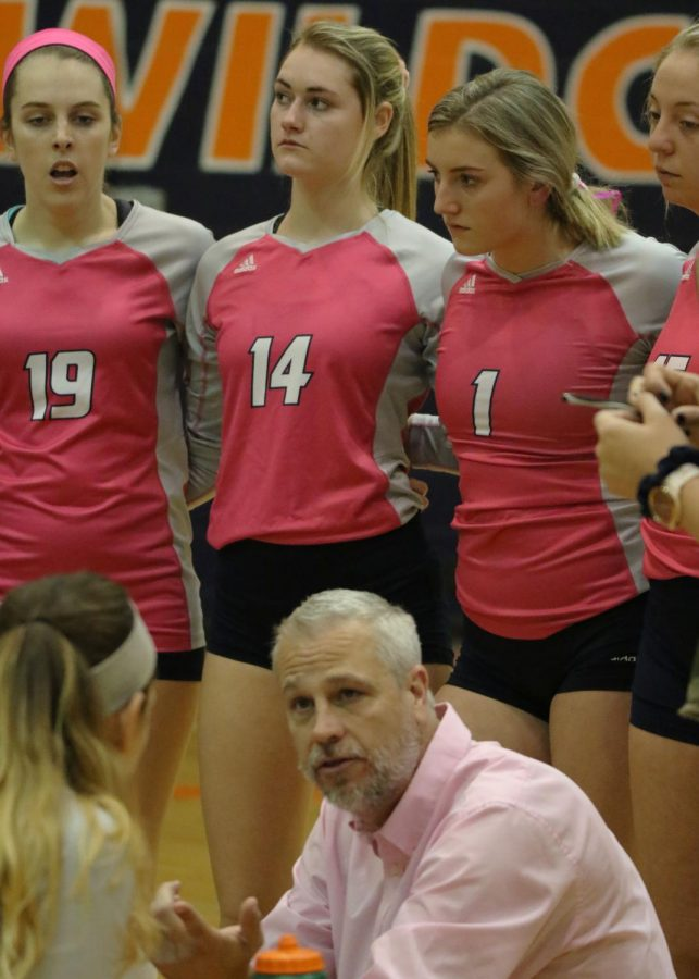 Head coach Matt Windle uses the time from a Ravens time out to organize movement on the court. The Wildcats sported pink jerseys for dig pink.