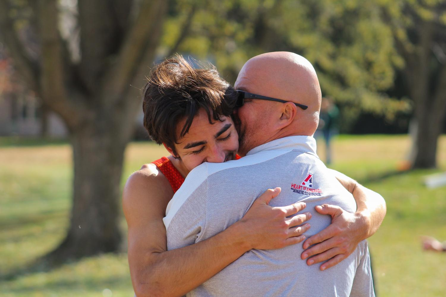 Senior Adam Preston embraces coach Tim Byers after his 12th place finish. Preston left it all on the course and finished fourth on the team, earning him a spot on the men's national squad of seven runners.