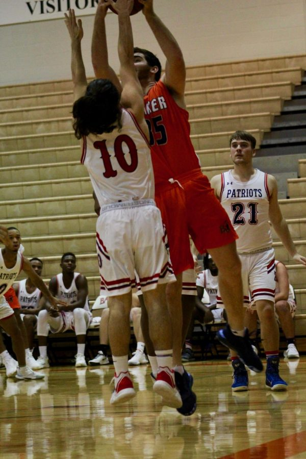Freshman Braden Wiggs fighting through an attempted block by a Baptist Bible College Patriot player. Wiggs assisted in the win with 16 points.