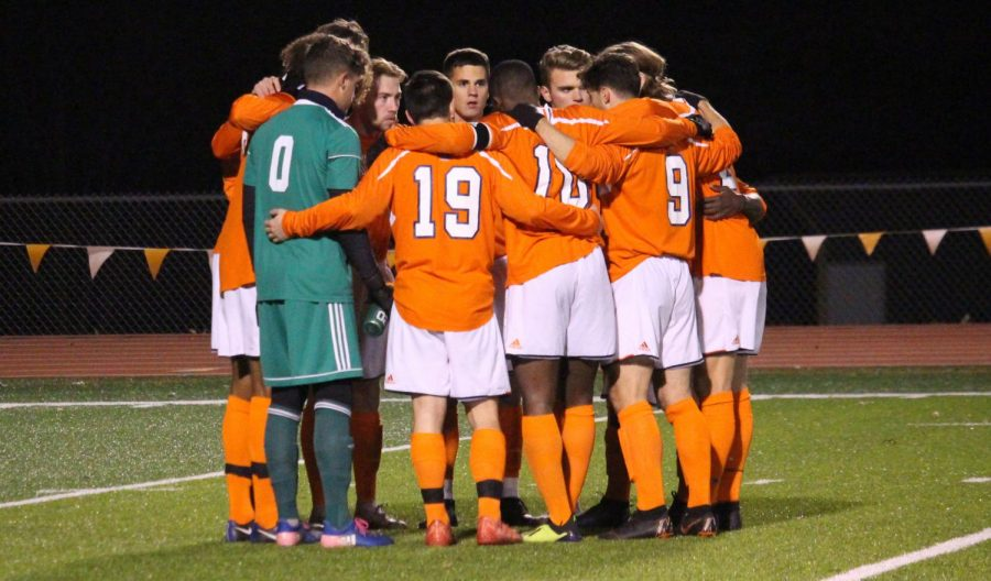 The Baker University men's soccer team devising a plan of action at the beginning of the soccer game.