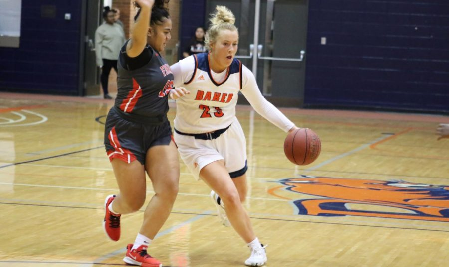 Junior Abby Bird drives to the basket to convert a layup. In three matches Bird accumulated 57 points, including 22 against Friend University in a 76-69 win.