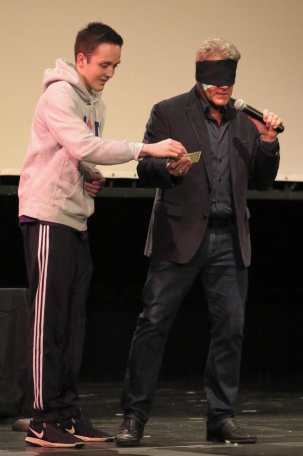 Freshman Zac Brehm confirms the numbers that mentalist Craig Karges is reading off while blindfolded. Karges used student participants for each routine.