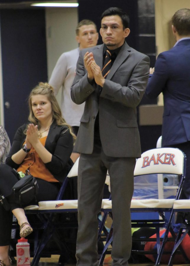 Head coach Cody Garcia cheers on 157 pound wrestler Colby Johnson against Benedictine. Johnson finishes his match 9-6 to extend Bakers lead.