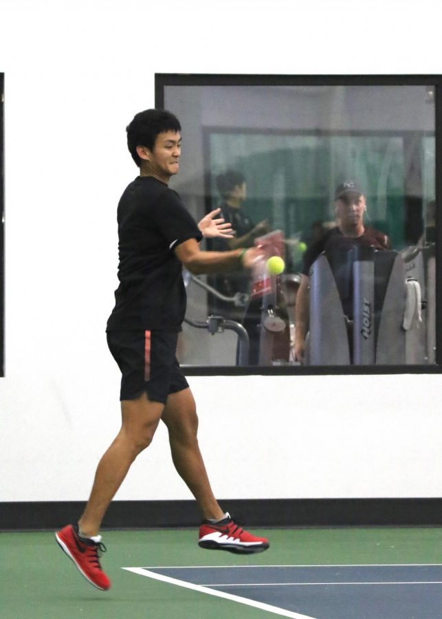 Senior Adam Ruckman returns a serve from a Cowley County Community College. Men's and Women's tennis played Feb. 1 at Genesis Health Club in Lawrence.