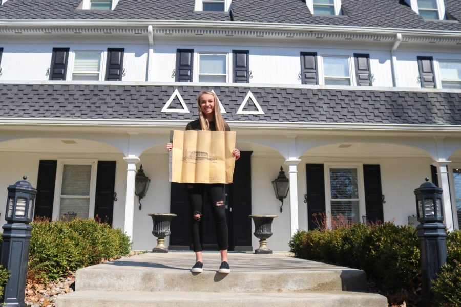 Junior Kaylee Smith, current president of the Baker University Delta Delta Delta sorority, holds up the original blueprints for the house. The blueprints were uncovered recently and are a memorable historical find for the member of the house.