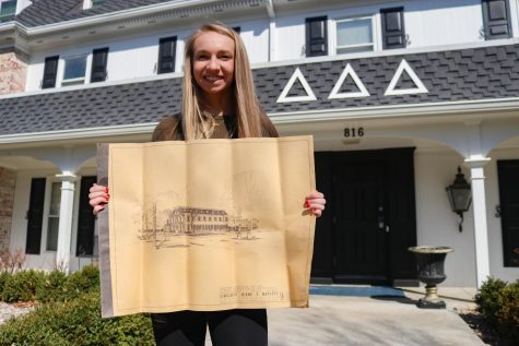 Junior Kaylee Smith, current president of the Baker University Delta Delta Delta sorority, holds up the original blueprints for the house. The blueprints were uncovered recently and are a memorable historical find for the members of the house.