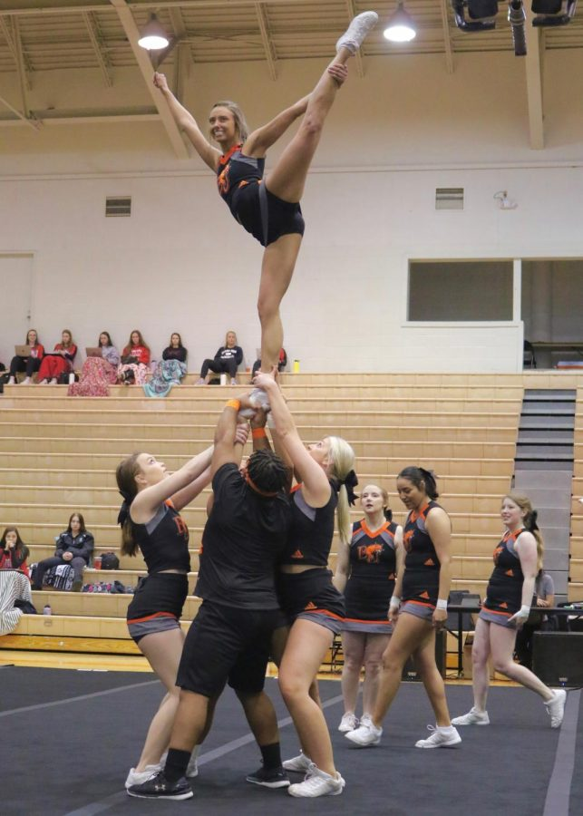 Junior Dara Underwood held by multiple cheer members during the Midwest Regional Qualifier in Collins Center.