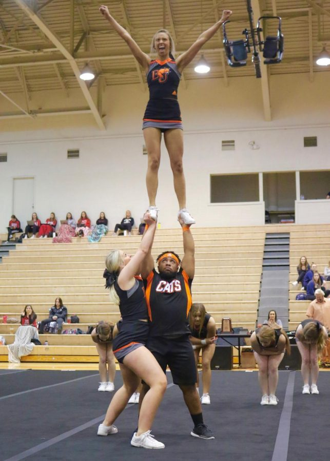 Sophomore Zayvion Ray is assisted by Senior Katie Branch to raise flyer and Junior Dara Underwood. Of the Wildcats cheer team, Underwood and Senior Bailey Stiffler are the designated flyers.