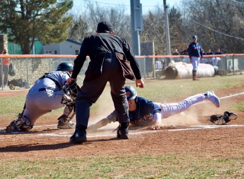 Senior Bailey Pattin sliding into home plate to score at Baker