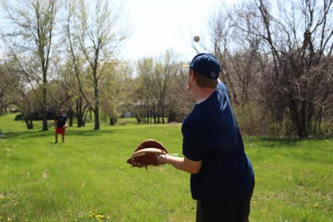 Baker University Baseball players, senior Martin Radosevic (left) and junior Donovan Sutti (right) play catch in their free time despite the impact that COVID-19 has had on their season.