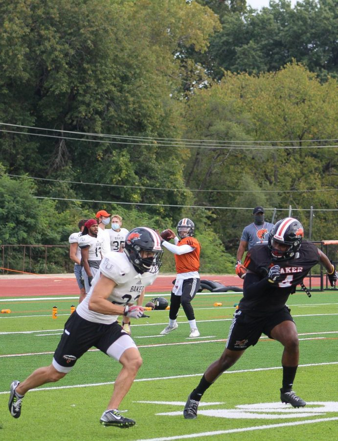 Quarterback Marco Aguinaga throwing to his receiver in coverage by the defensive back, Will Cox.