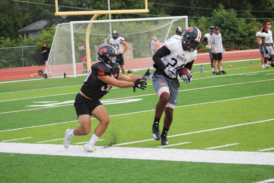 Wide receiver, Jordan Green works to stay in bounds after catching the ball in coverage.