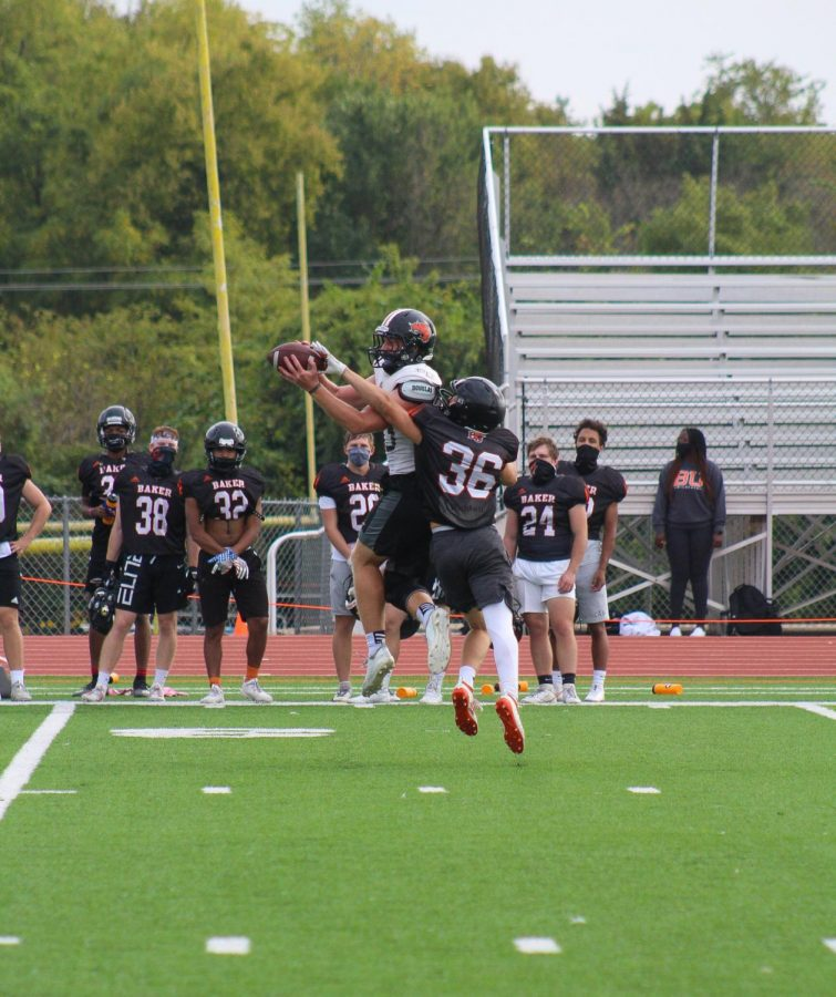 A Wildcat receiver makes the catch as defensive back, Colton Hutchinson, provides coverage on the play.