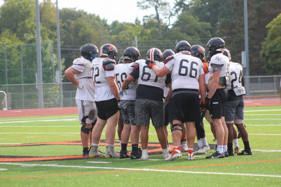 The Wildcat offense gathers in a huddle to discuss their next play.