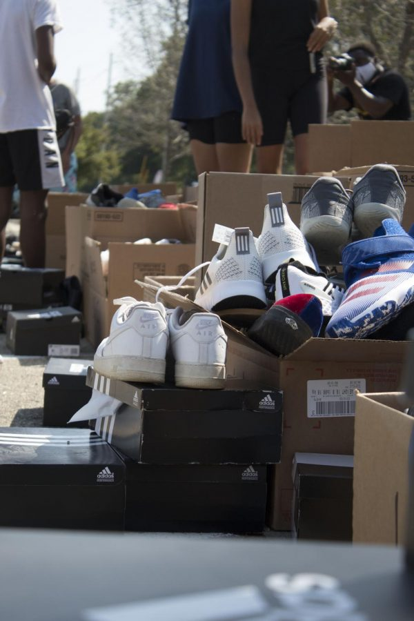 Boxes overflow with shoes. Shoes varied through mens and womens sizes.