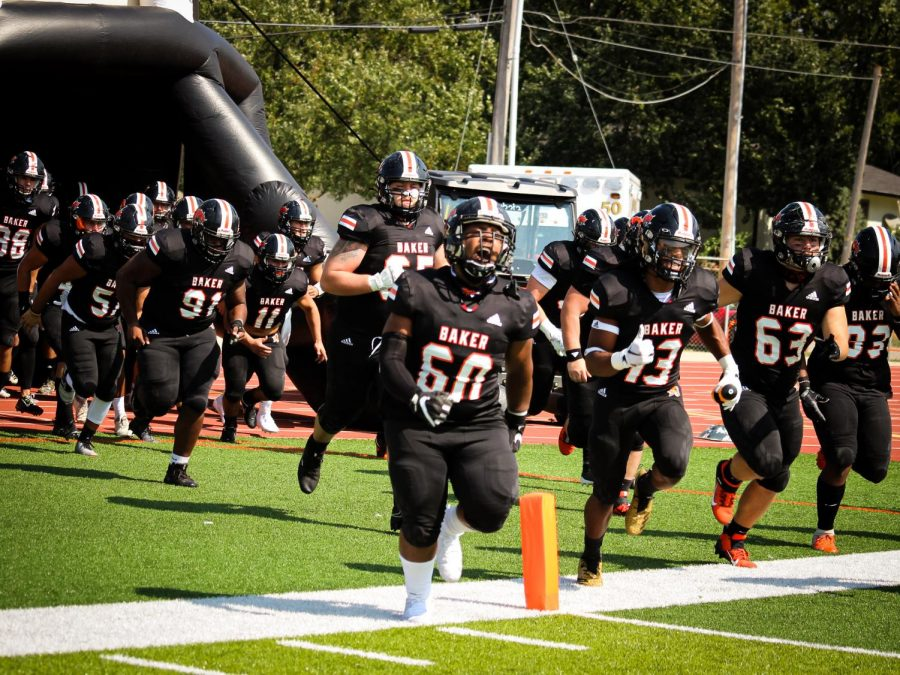Offensive lineman Evan Bishop runs with the Baker football team in their iconic entrance through an inflated helmet.