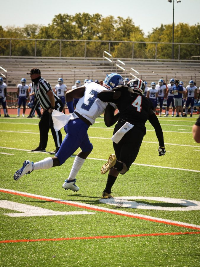 Defensive back Will Cox  blocks Peru State's wide receiver Garry Fleming.