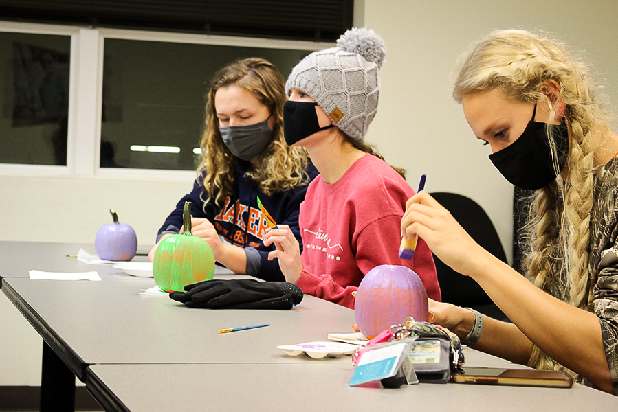 Sophomore Savannah Nott, Junior Macey DeWeese and Junior Elaena Steffen worked on their pumpkins while engaged with Mungano's presentation. Mungano presented on Halloween's role in culture appropriation.