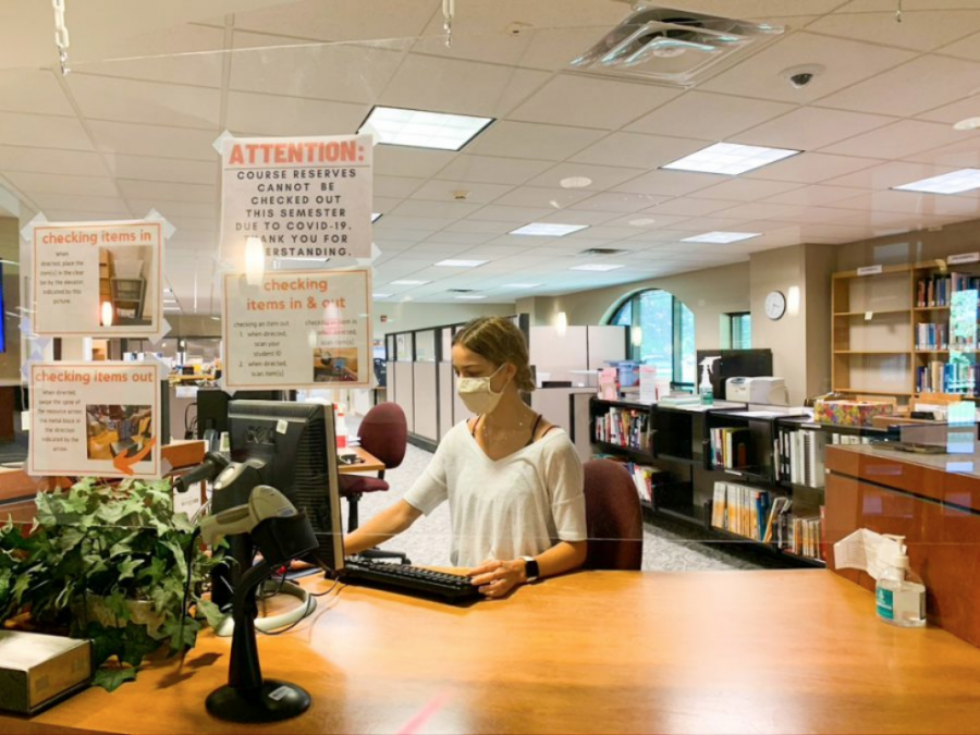 Senior Ashley Pippin sits at the circulation desk inside Collins Library. As part of the Work Study Program, students at Baker can apply to work as a Library Assistant.