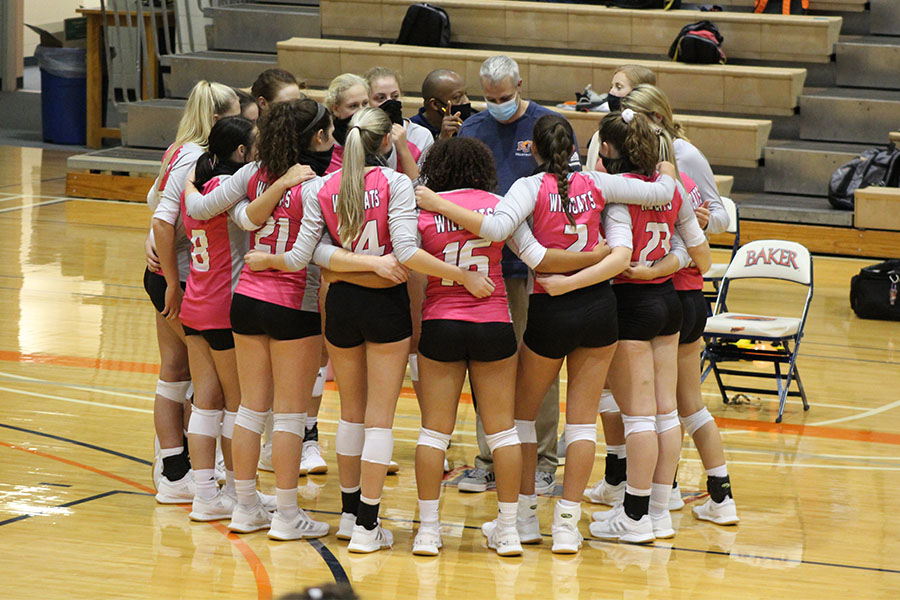 The Baker Volleyball team huddling together during a break in the game. While the Wildcats played a strong game, MidAmerica Nazarene University ended up taking the victory with a final score of 3-1.