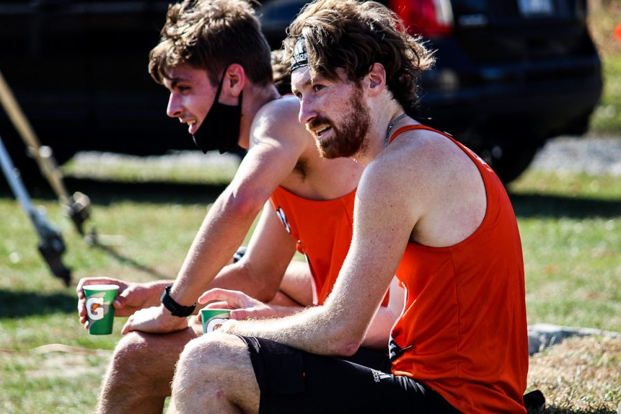 Senior Grant Roesner and Junior Ty Packard watch as the rest of their teammates finish the 8k race.