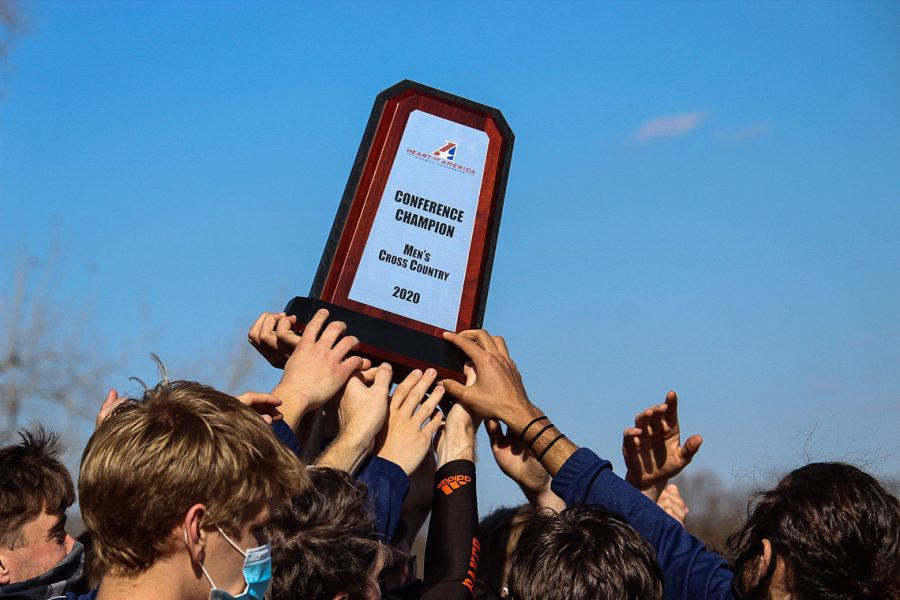 The Men's Cross Country team holds up their plaque in celebration of winning the Conference Championship.