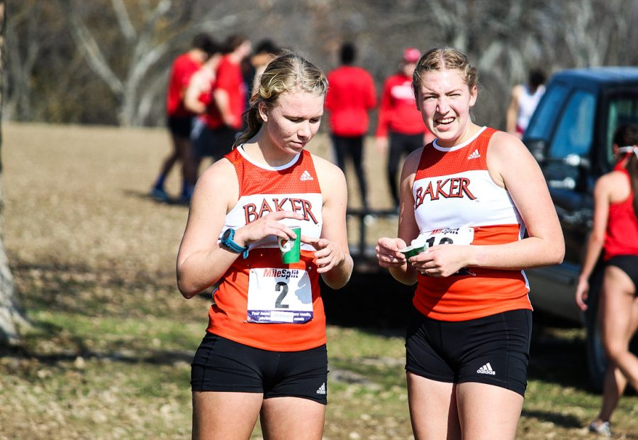 Freshmen Blaise Ball and Peyton Sannan recover after their race and watch the rest of the runners finish.