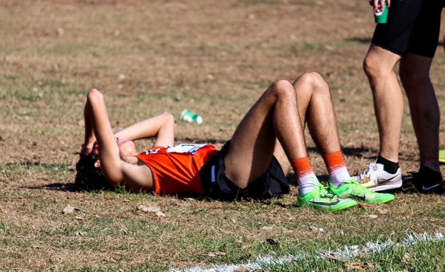 Junior Maxx Bradley recovers after a fast finish in the Cross Country Conference Finals.