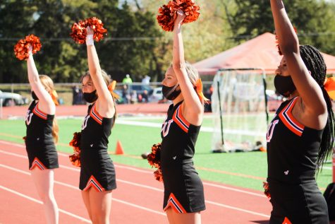 Members of the cheer team performing on the sidelines during the game.