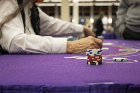 A dealer handles cards while a stack of chips awaits the hand