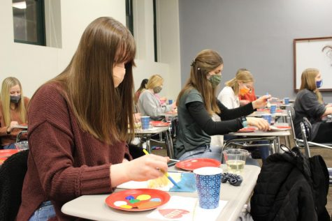 "Senior Marissa Neumer follows the Bob Ross tutorial titled ""Sunset Aglow."""