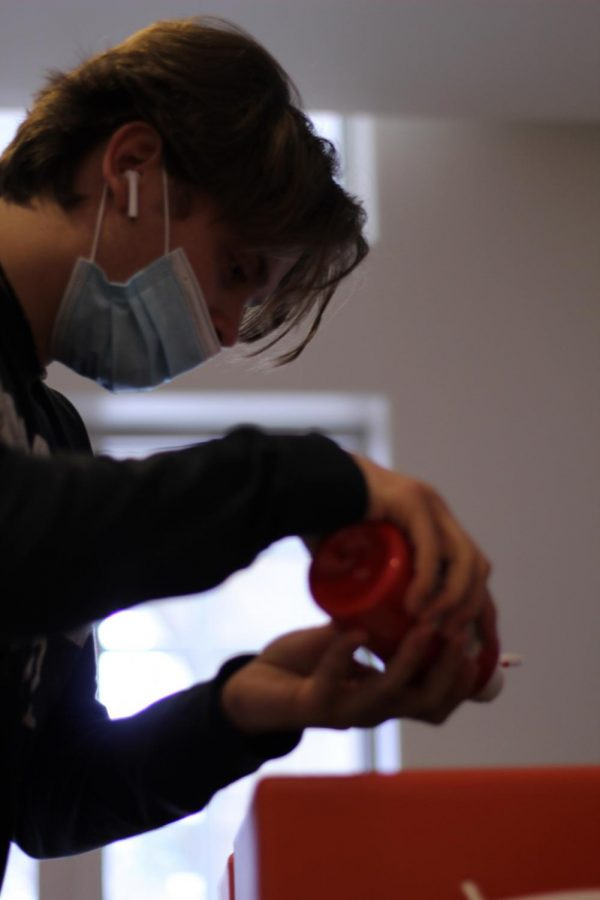 Burnette concentrates as he adds red paint to his frisbee.