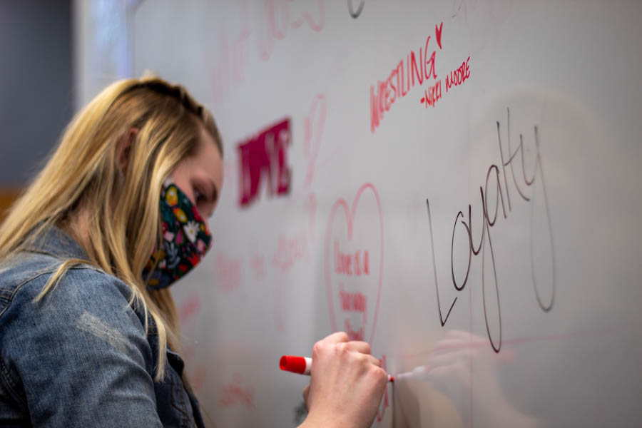Freshman Celbi Richardson adds to the collection of what love means to Alpha Chi Omega by writing on the whiteboard.