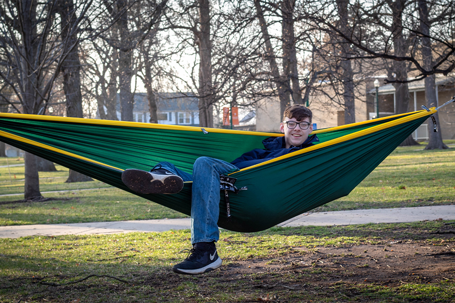 Freshman Kyle Newman, leader of the hammocking club, relaxes in his hammock on campus.