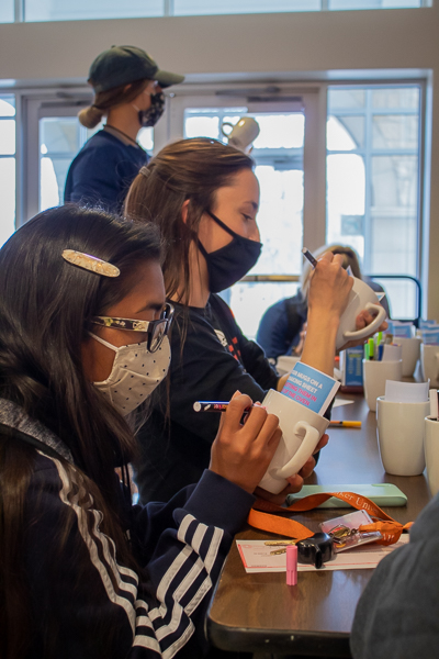 Sophomore Natalie Gonzalez, Junior Mia Wilhoit and Sophomore Emma Ancira continue to design their mugs with markers provided by SAC.