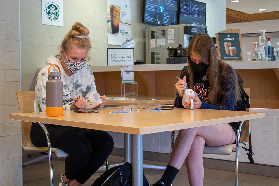Sophomores Parker Straight and Riley Zook put their artistic abilities to the test as they sit outside of The Daily Grind.