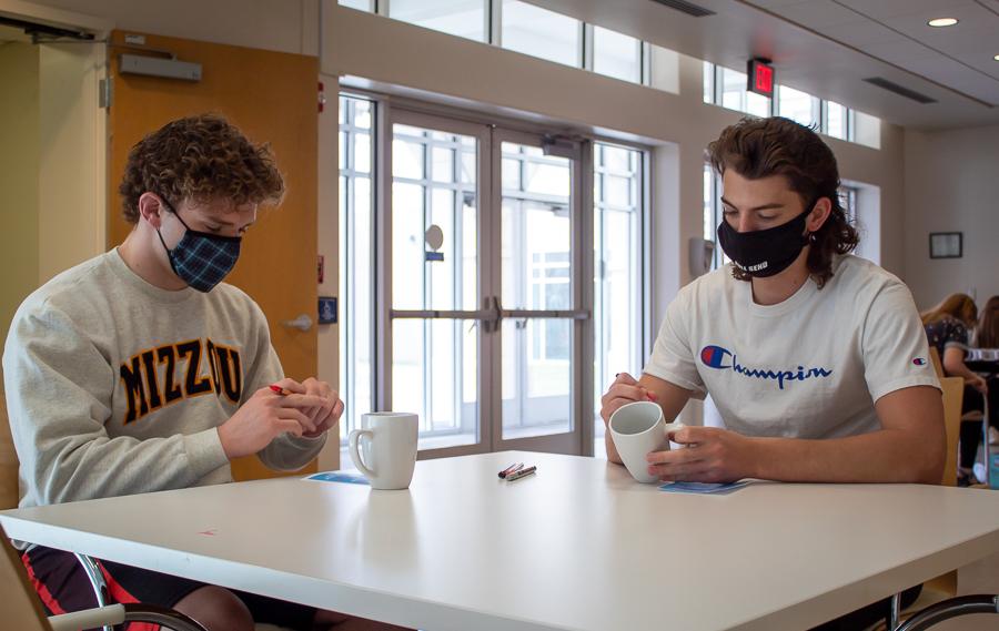 Freshmen Caleb Nelson and Roman Bushek prepare to decorate their mugs.