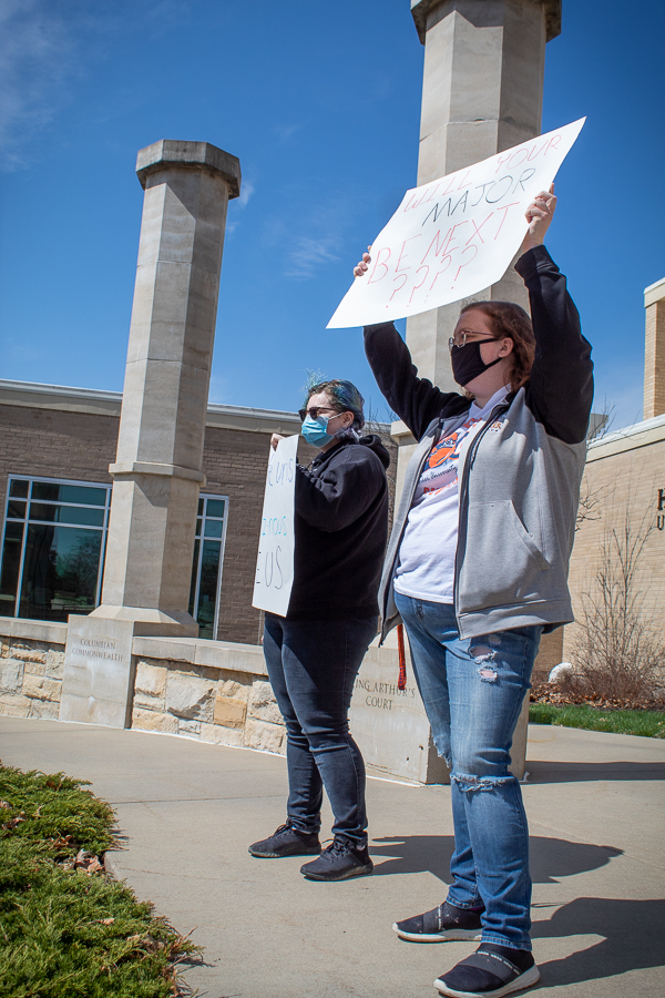 Gardner and Sophomore Kathryn Harman hold up their signs to bring awareness to the subject.