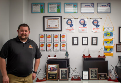Randy Flowers standing in front of only a few of many awards he has been given during his time at Baker University.