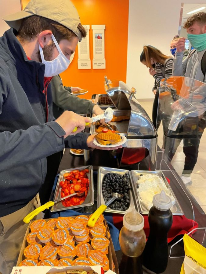 Students line up to grab waffles from the SAC table. In addition to plain waffles, students could add chicken, strawberries, blueberries, whipped cream, butter, peanut butter or syrup to their stack.