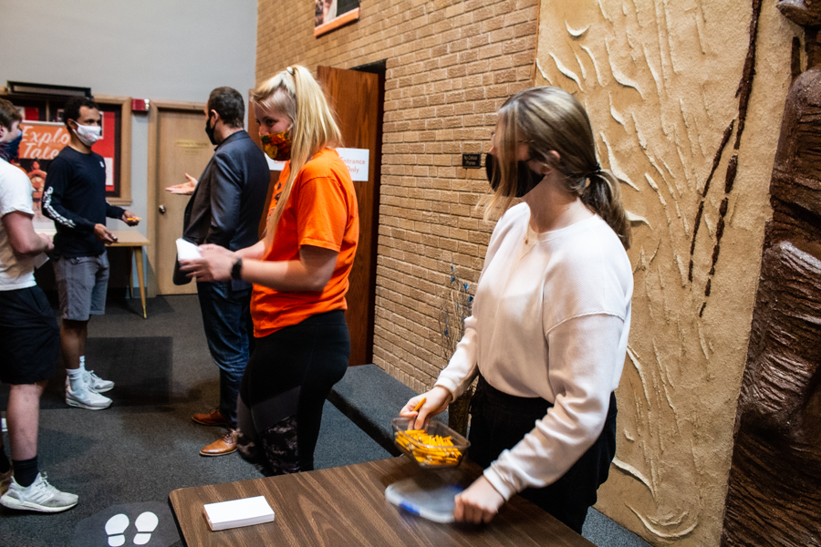 Junior Madi Martin (left) and Sophomore Ashley Daub (right) hand out paper and pencils to students as they enter into Rice Auditorium. Mentalist Chris Carter involved the audience by having them write different things on the paper during his performance.