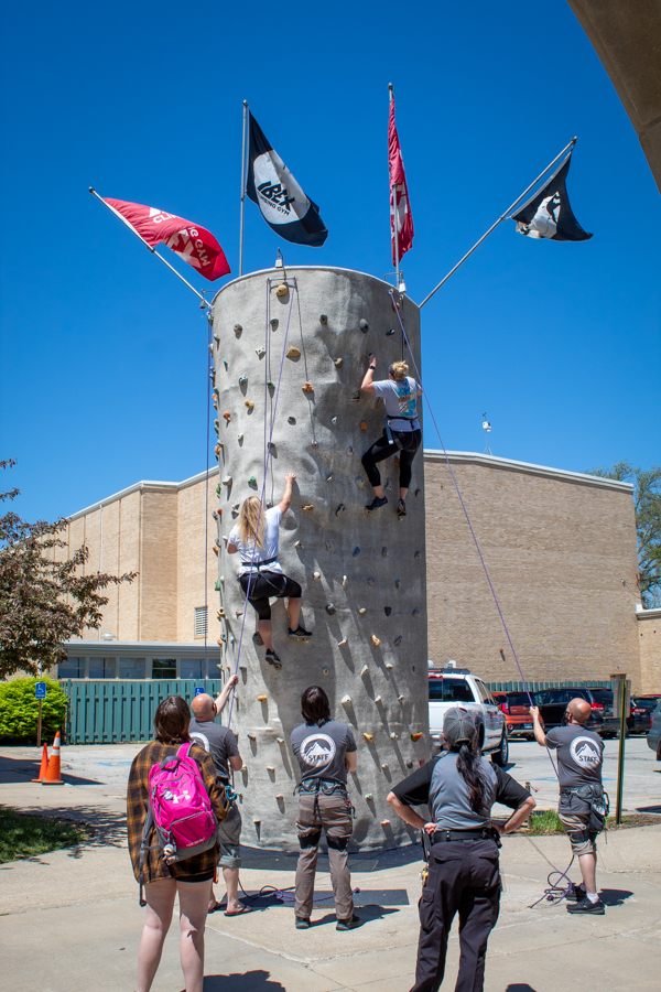 Athletic Trainers Sarah Edwards, left, and Amanda Smith, right, take advantage of the rock wall provided by SAC as students and staff watch.
