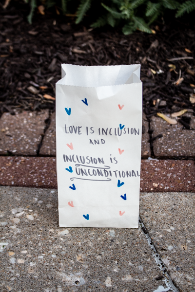 """A paper bag sits behind the speakers to show support of """"A Night  of Unity."""""""