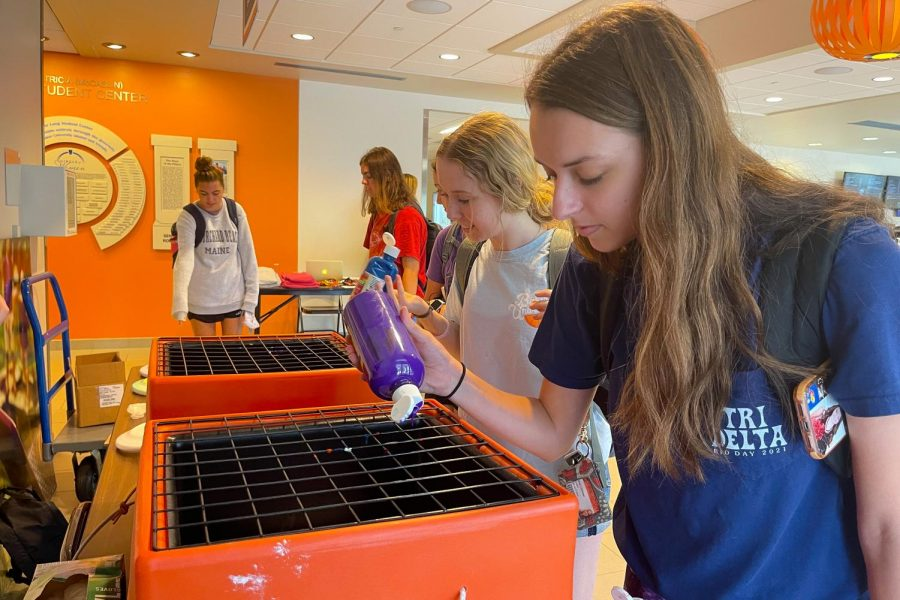 Freshmen Olivia Chrisman (left) and Wrenn Paden (right) try out different techniques with paint during SACs spin art event.